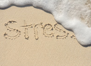 stress written in the sand and getting washed away by a wave