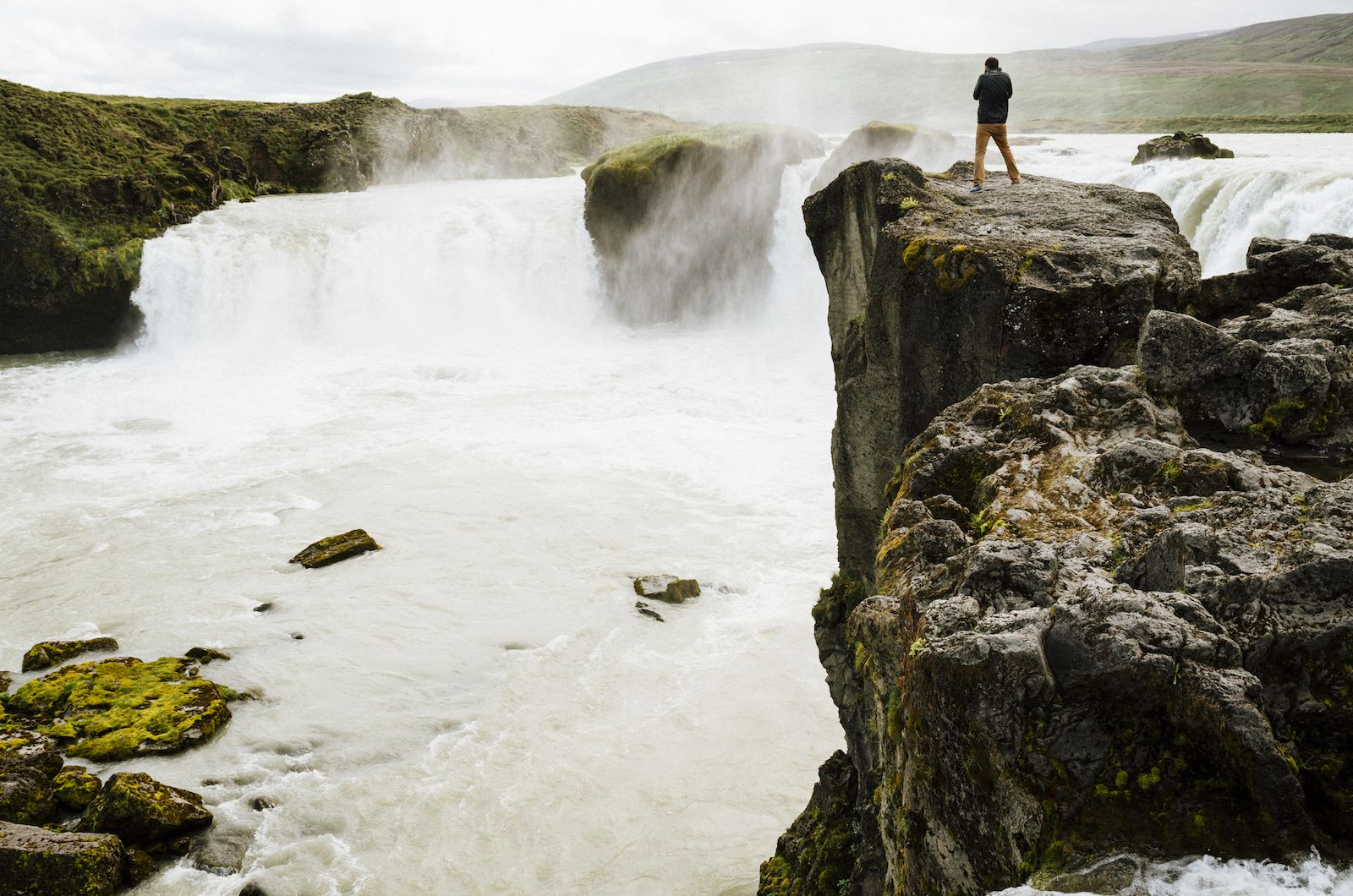 man overlooking a waterfall from a nearby cliff