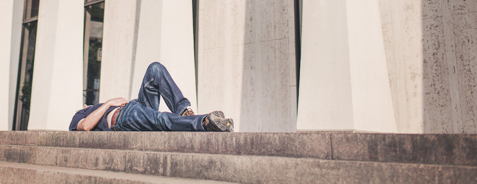 young man laying on the steps of an office building